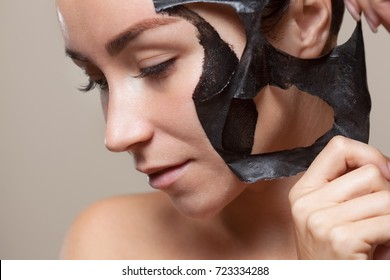 a black mask to the face of a beautiful woman. Spa treatments and care of the cats in the beauty salon.