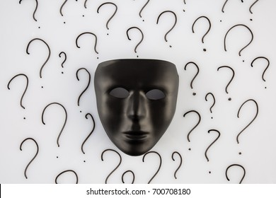 Black mask on  white background with black question marks. Who am I ? concept
