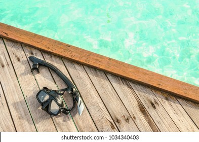 Black mask for snorkeling on a wooden spot against azure water
