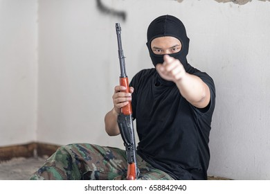 Black masked Robber in the black shirt and camouflage pant is sitting on the floor and hold the gun in his hand. He is pointing to camera. Selective focus at his face.