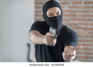 Black masked Robber in the black shirt with a gun holds his hand out for the money, concept of danger, threat and extortion. Selective focus at his face.