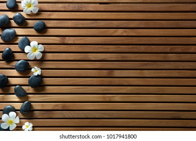 black massage pebbles and spa flowers set on design wooden board for zen spa, hammam, sauna or pure shower, copy space still life, above view