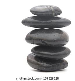 Black massage stones stacked, isolated on white