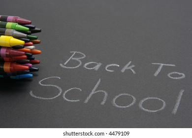 "Black material with words ""Back To School"" written in crayon and a bunch of crayons to the side."