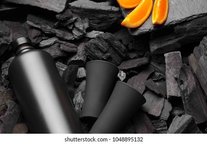 Black matte bottle of vodka or tequila and shot glass .Slices of oranges.On charcoal background. Black edition.Creative.Let's drink.Cheers.Copy space
