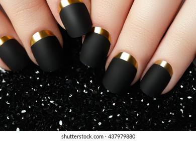 Black matte nail polish. Manicured nail with black matte nail polish. Manicure with dark nailpolish. Golden nail art manicure