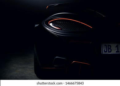 Black Mclaren 570s rear left tail light illuminated, shot against a dark background featuring a rear wing mounted to the car.