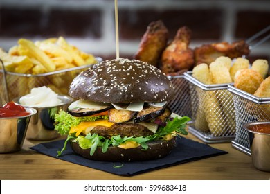 Black Mediterian Burger with Aubergine and Parmesan Frying basket with Mozzarella Stick, Chicken Wings, Chicken Nuggets and Fries