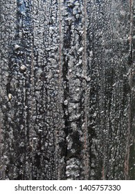 a black melting old bitumen preservative covered textured wooden surface