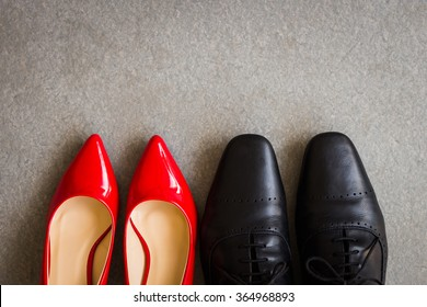Black men shoes and red women shoes on gray background