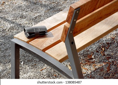 Black mens wallet lying outdoors on a wooden bench.