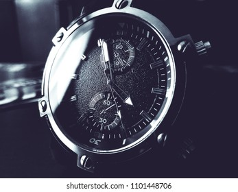 Black mens watch with steel case and light reflection on the dial