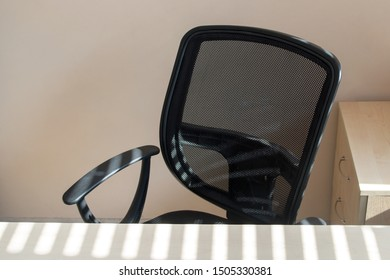 A black mesh-backed office armchair facing a beige-painted wall behind a table next to a wooden nightstand, sunlight streaming through the blinds onto the chair and desk