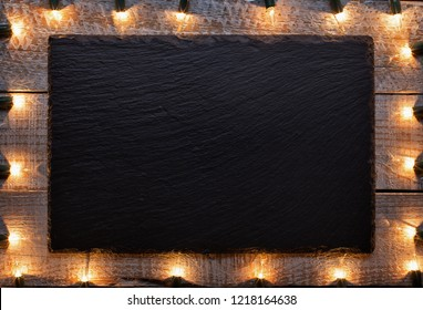 Black message board surrounded by old christmas decorative lights on battered wooden surface - copy space