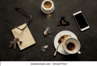 Black messy cafe table - empty coffee cup, book, mobile phone (smartphone), glasses and keys. Dark moody layout captured from above (flat lay, top view).