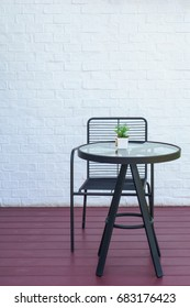 black metal chair and table on the wooden floor with white brick wall background.