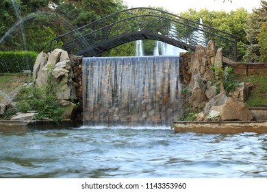 Black metal decorative bridge across fountain with waterfalls at sunset in a park in Pyatigorsk, Russia
