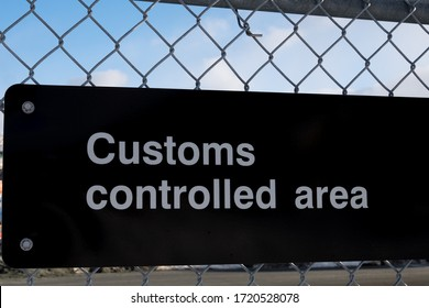 A black metal display sign with customs controlled area written in white letters. The sign is attached to a metal chain link wire fence. The background has blue skies and white clouds.