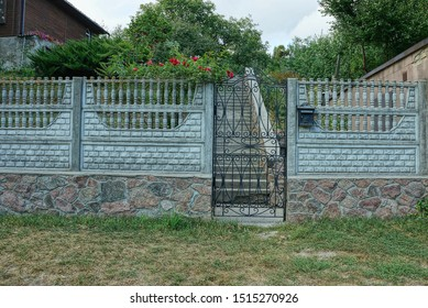 black metal door and gray concrete fence in the street in green grass