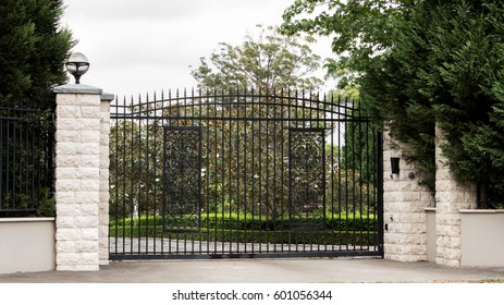 Black metal driveway entrance gates set in brick fence