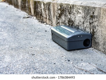 Black Metal external rodent rat bait station outside against a wall close up.  Pest Control.