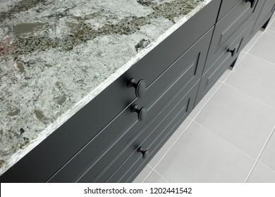 Black metal handles on wooden drawer and front door of kitchen cabinet under stone worktop .