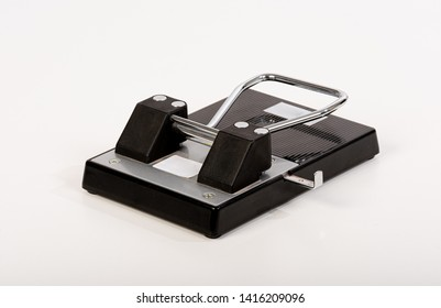 Black metal hole-puncher on a light grey table.