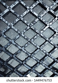 Black metal lattice of perfect shape covered with water drops