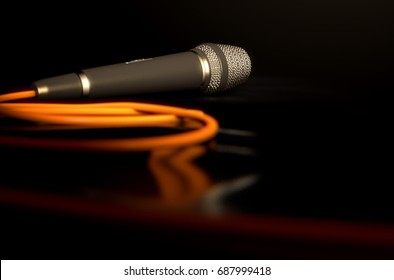 A black metal microphone on laying on a dark stage floor with its cord connected
