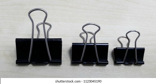 Black metal paperclip on cream wooden background.