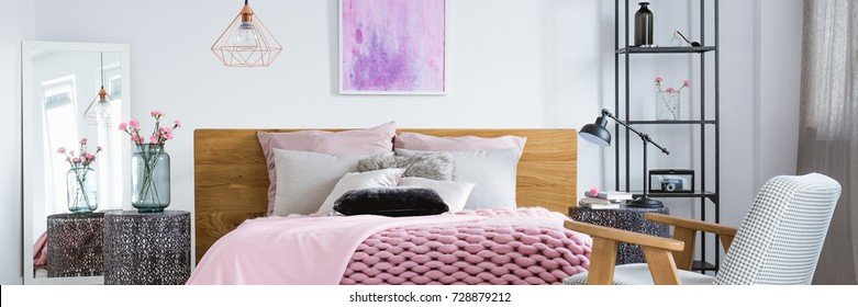 Black metal rack with decorations standing by a bed with cushions in tidy bedroom