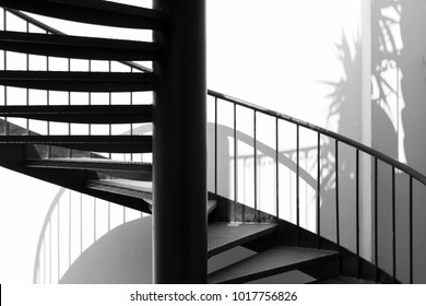 Black Metal Round Stair with white wall and shadows. Stairway, staircase, stairwell, flight or simply stairs is a construction designed to bridge a large vertical distance by dividing it into smaller.