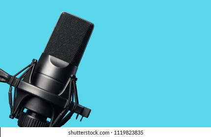 Black metal studio condenser microphone. Side view. Isolated on blue background