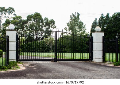 Black metal wrought iron driveway property entrance gates set in brick
