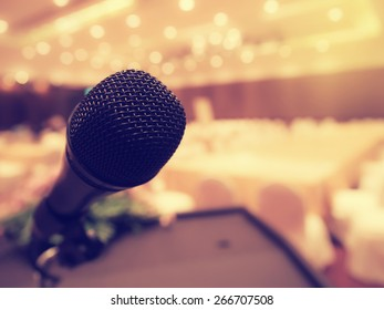 Black microphone in concert hall or conference room with defocused bokeh lights in background. Extremely shallow dof.  : Vintage style and  filtered process.