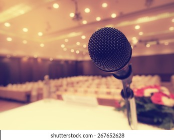 Black microphone in concert hall or conference room with defocused bokeh lights in background. Extremely shallow dof.  : Vintage style and  filtered process