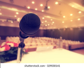 Black microphone in  empty conference room or concert hall  with defocused bokeh lights in background. Extremely shallow dof.  : Vintage style and  filtered process.