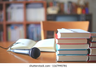 Black microphone on the table in the training room. Many books are stacked next to each other bookshelf is the background selective focus and shallow depth of field