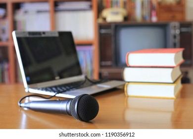 Black microphone on the table in the training room. Book stack with notebook computer as background selective focus and shallow depth of field