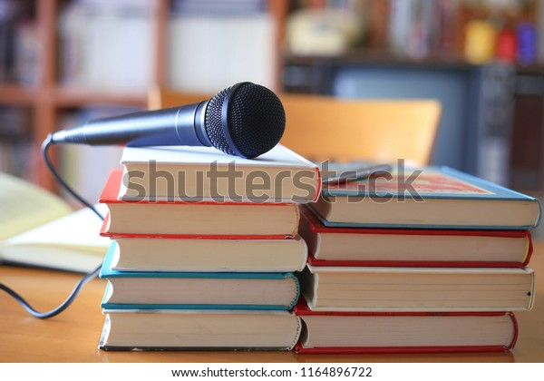 Black microphone placed on several books stacked n the training room bookshelf is the background selective focus and shallow depth of field