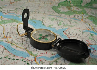 Black, military compass on the detailed map.