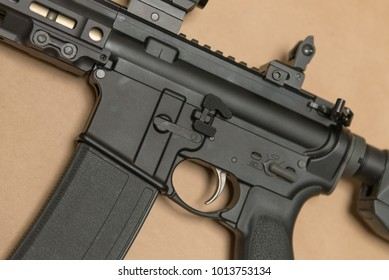 Black Military Style Assault Rifle on brown background close up trigger left side