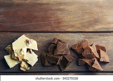 Black, milk and white chocolate pieces on color wooden background