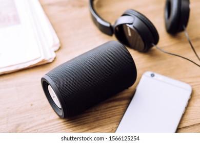 Black mini wireless portable bluetooth speaker for music listening.