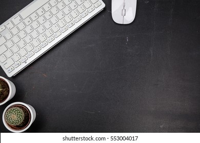 Black minimal office desk table with white wireless computer mouse and keyboard. Top view with copy space, flat lay.