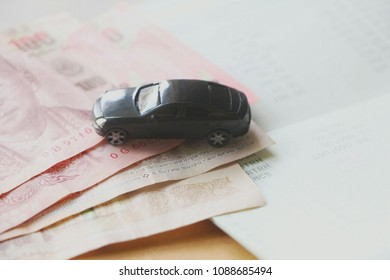 black miniture car on  money.