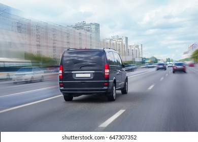 black minivan is moving on the highway in the city