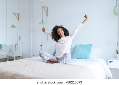 black mix race woman on bed stretching
