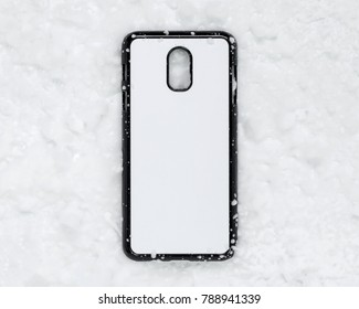 Black mobile cover on snow texture background. Phone case and white surface for printing.