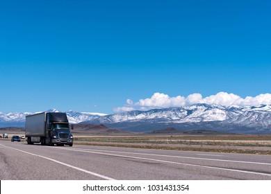Black modern big rig semi truck with big cab for long distance haul transporting commercial goods in dry van semi trailer going on the freeway in Utah passes mountains in snow